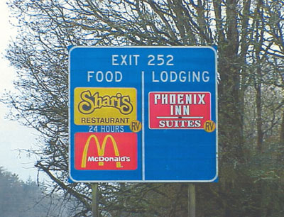 Highway sign showing the use of the RV Friendly symbol on a food-lodging sign.  The symbol is placed directly in the corner of the emblem it modifies.