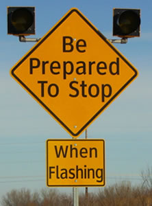 "An image of a diamond-shaped warning sign with the legend ""Be Prepared To Stop"" with a rectangular plaque below with the legend ""When Flashing."" Both legends are displayed in upper- and lower-case letters of the alternative alphabet."