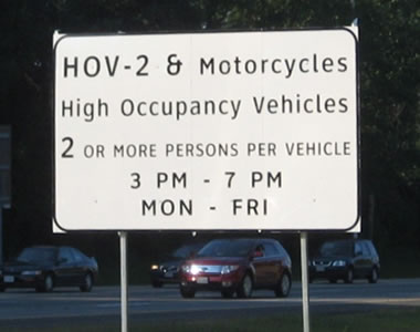 An image of a rectangular regulatory sign for high-occupancy vehicles. The legend is displayed in upper- and lower-case letters of the alternative alphabet.