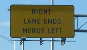 "The photograph at center right is a rectangular warning sign that displays the legend ""RIGHT LANE ENDS MERGE LEFT"" in the alternative alphabet in a negative-contrast orientation."