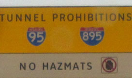 "The photograph at lower left is a rectangular regulatory sign that displays the legend ""TUNNEL PROHIBITIONS - NO HAZMATS"" in the alternative alphabet in a negative-contrast orientation."