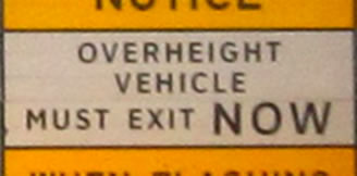 "The photograph at lower right is a rectangular regulatory sign that displays the legend ""OVERHEIGHT VEHICLES MUST EXIT NOW"" in the alternative alphabet in a negative-contrast orientation."