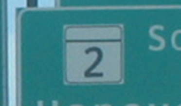 An image of a portion of a sign with a State marker is shown using the alternative letter style to display the numeral.