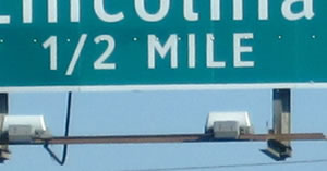 "An image of a guide sign distance legend of ""½ MILE"" is shown. The numerals and solidus of the fraction are aligned as a single line instead of the numerals being arranged diagonally about the solidus."