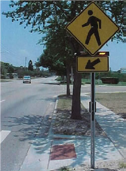 An image diplaying an example of Rectangular Rapid Flashing Beacons with W1-2 sign and W16-7p plaque at crosswalk across uncontrolled approach. [Photo courtesy of City of St. Petersburg, Florida]
