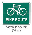 "Pedestrian and Bicycle Sign ""BICYCLE ROUTE (D11-1)"" is shown as a horizontal rectangular green sign with a white border and legend. It shows a symbol of a bicycle above the words ""BIKE ROUTE."""
