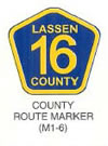 "Guide Sign ""COUNTY ROUTE MARKER (M1-6)"" is shown as an upward-pointing blue pentagon, with a yellow border and legend. The word ""LASSEN"" above the large numerals ""16"" and the word ""COUNTY"" are shown on three lines. The sign is labeled ""County Route Sign."""