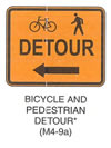 "Pedestrian and Bicycle Sign ""BICYCLE AND PEDESTRIAN DETOUR (M4-9a)"" is shown as an orange sign with a black border and legend. It shows symbols for a left-facing bicycle and left-facing walking person on the top line, the word ""DETOUR"" on the middle line, and a horizontal left-pointing arrow on the bottom line. This sign was anticipated for inclusion in the 2003 edition of the MUTCD at the time of this printing."