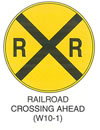 "Railroad and Light Rail Transit Grade Crossing Sign ""RAILROAD CROSSING AHEAD (W10-1)"" is shown as a round yellow sign with a black border and legend. A black ""X"" covers the sign, and two ""R's"" are shown in the left and right quadrants of the sign."