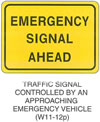 "Warning Sign ""TRAFFIC SIGNAL CONTROLLED BY AN APPROACHING EMERGENCY VEHICLE (W11-12p)"" is shown as a horizontal rectangular supplemental plaque with the words ""EMERGENCY SIGNAL AHEAD"" on three lines."