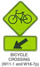 "Pedestrian and Bicycle Sign ""BICYCLE CROSSING (W11-1)"" Is shown again with W16-7p sign shown directly below it. W16-7p is shown as a horizontal rectangular green sign with a black border. It shows a diagonal black arrow pointing down and to the left."