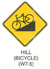 "Pedestrian and Bicycle Sign ""HILL (BICYCLE) (W7-5)"" is shown as a diamond-shaped yellow sign with a black border. It shows a black symbol of a bicycle pointing to the left and down on a ramp that slopes up from left to right."