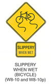 "Pedestrian and Bicycle Sign ""SLIPPERY WHEN WET (BICYCLE) (W8-10)"" is shown as a diamond-shaped yellow sign with a black border. It shows a black symbol of a bicycle at a slight angle pointing down and to the left. Two vertical wavy lines are shown extending down from the bicycle tires. Directly below W8-10p is shown as a horizontal rectangular yellow sign with a black border. It shows the words ""SLIPPERY WHEN WET"" in black on two lines."